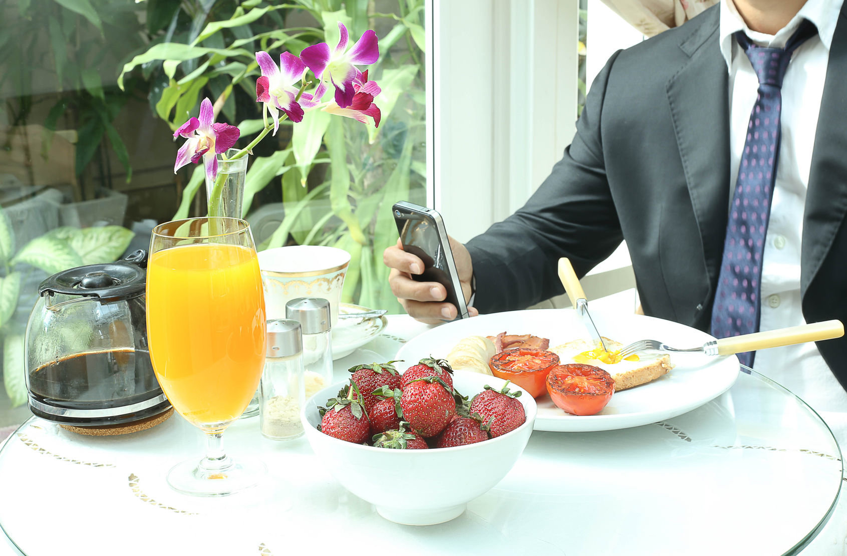 38968037 - businessman using mobile phone working while having a breakfast
